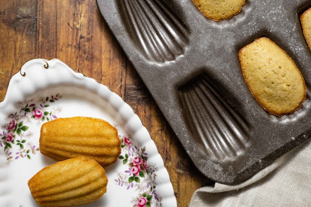 unmolding the madeleines onto a platter