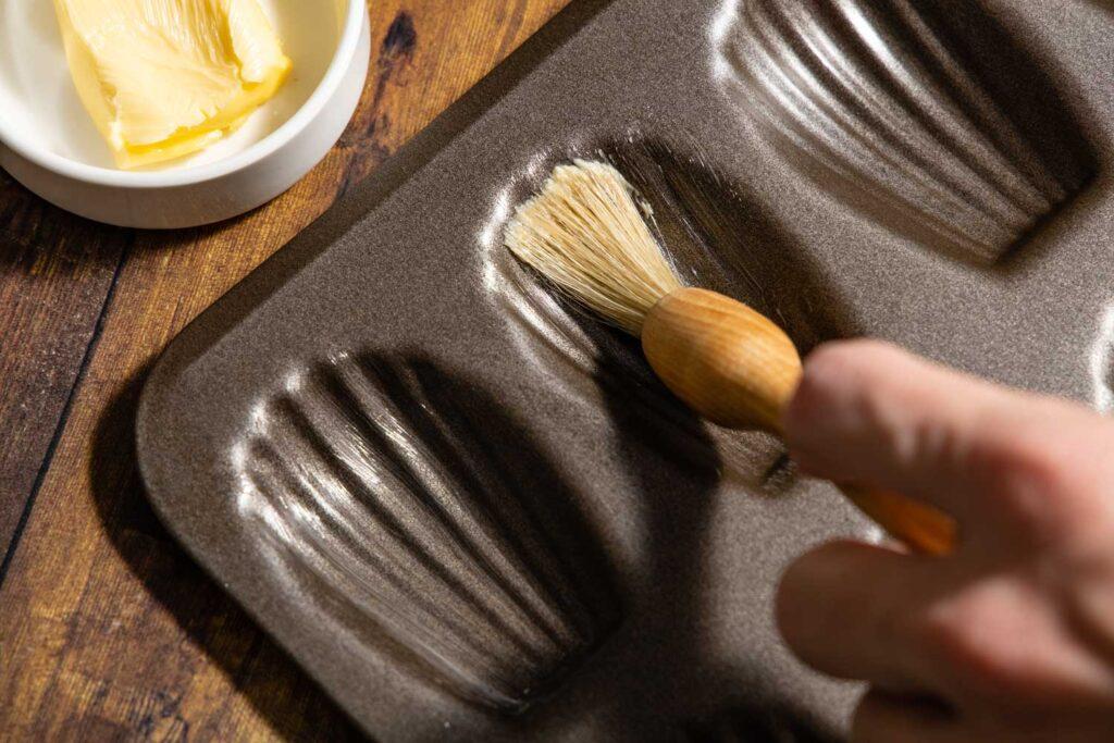 buttering a madeleine pan