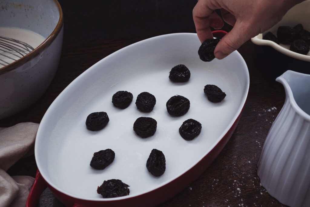 putting brandy-soaked prunes in a baking dish