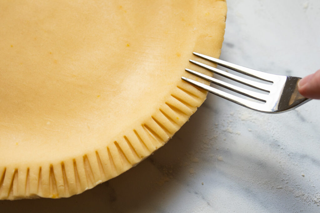 crimping the edges of the tart with a fork