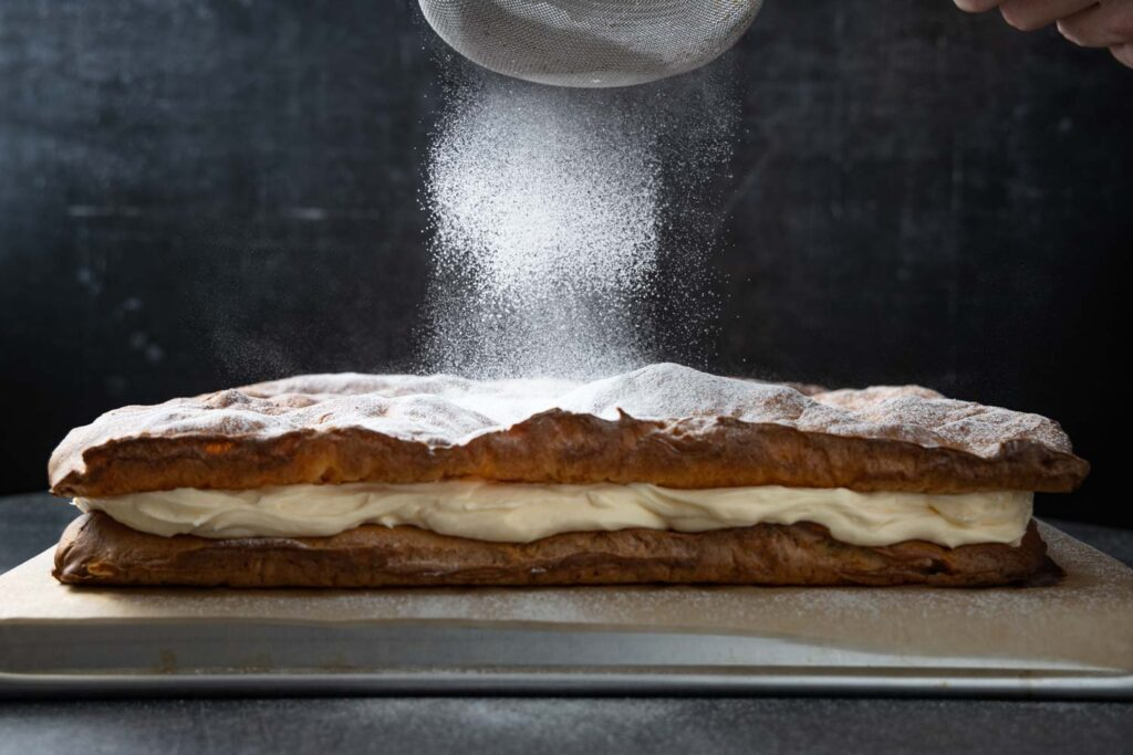 dusting the karpatka with confectioners' sugar