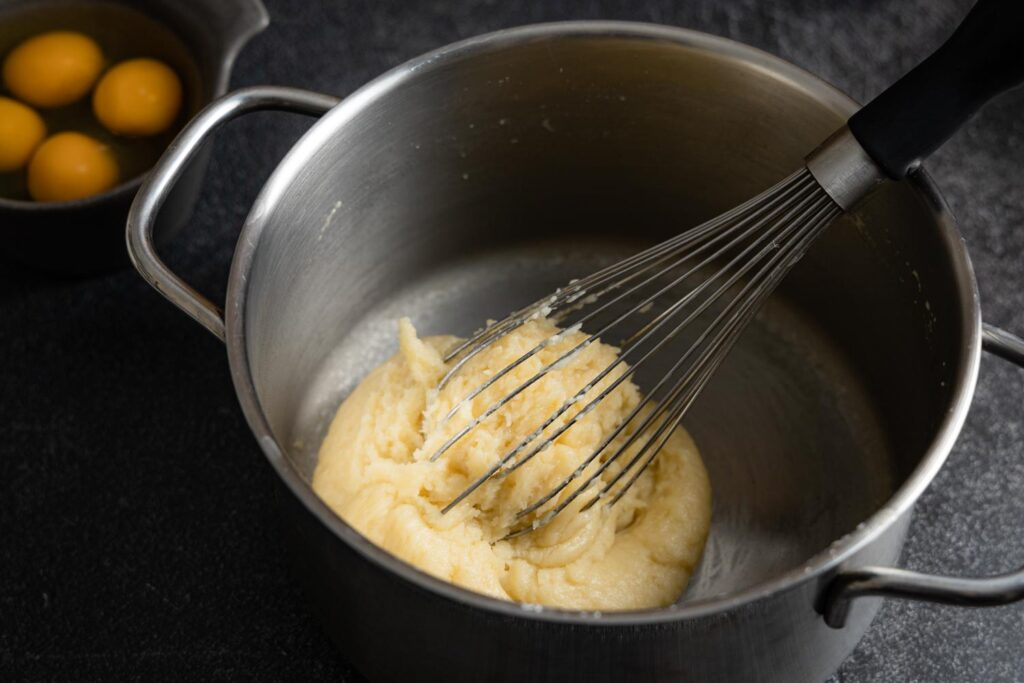 choux paste in a saucepan with a whisk and eggs in a prep bowl
