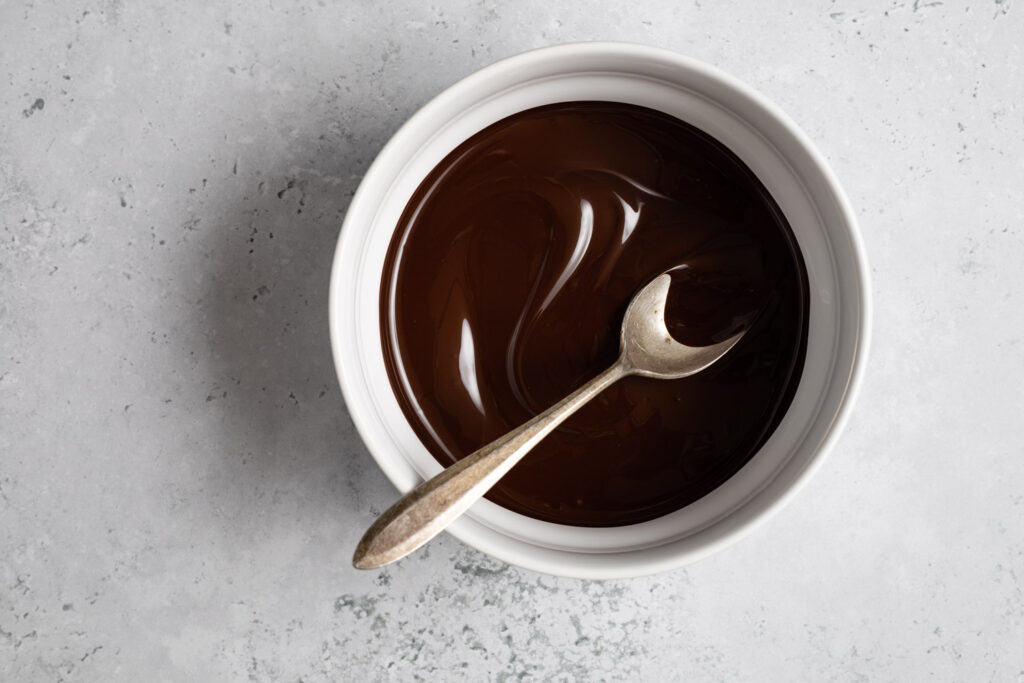 melted chocolate in a white bowl with an antique spoon
