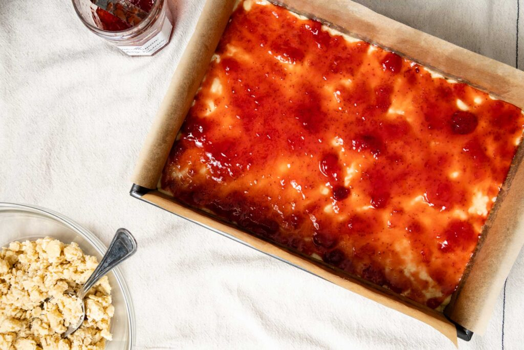 spreading strawberry jam on shortbread dough